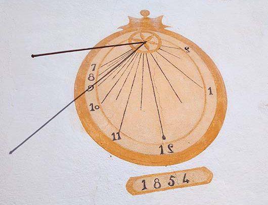 rellotge vertical de forma ovalada i amb gnòmon de vareta